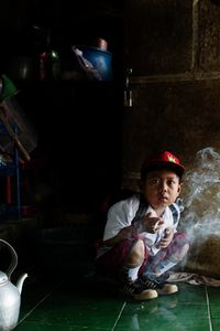 Dihan Muhamad, who used to smoke up to two packs of cigarettes a day before cutting down, has his first cigarette at 7AM at his home before he attends his first grade class in his village near the town of Garut in West Java, Indonesia. © Michelle Siu