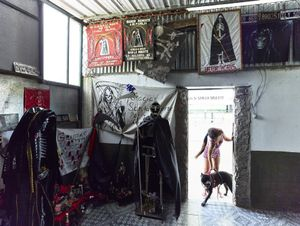 Young girl responsible of the San la Muerte temple in the Buenos Aires suburbs of San Vicente, with her dog