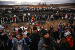Protestors raise their arms during a prayer at an action defending what they claim to be a sacred site near Turtle Island against construction of the Dakota Access Pipeline in Cannon Ball, North Dakota in November 2016.