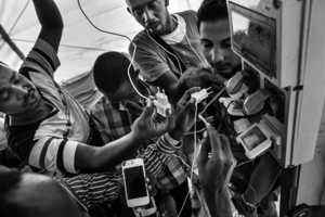 African and Syrian guys recharging their phones after the long sea journey crossing the Mediterranean, at the reception center at the Sicilian port of Augusta on June 20, 2016.