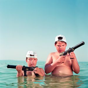 Two children hold toy guns at the lake.