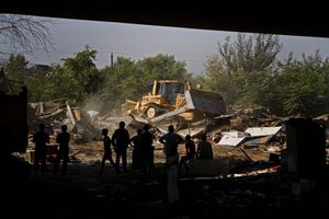 Bulldozers flatten homes in the Nova Gazela settlement while families, social workers and police watch from under the Gazela bridge. © Matt Lutton