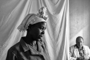This young woman awaits a second opinion about her child, a referral from the first doctor to a pediatrician, their offices and examining rooms separated by this draped bed sheet.                                   © Lola Reid Allin