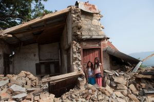 Dipa(left) and Parboti are sister, stand in front of their broken house in Gorkha district, Nepal.