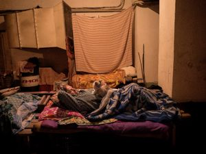 A refugee with her cat preparing for the night in a Donetsk bomb shelter.