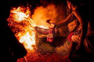 Unable to erect himself supporters drag the Theyyam performer from the fire so he can continue with the ceremony.