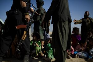Children wait to receive the first loaves of bread from an Afghani-American woman handing out food and clothing at an Internally Displaced Persons (IDP) camp, called Charhi Qhambar, on the edge of Kabul. Most of the IDPs here are from Kandahar and Helmand provinces. Most families have lost at least one family member from American bombs. © Michael Christopher Brown