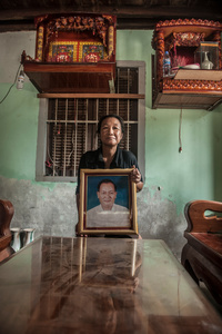 Lim Sokphiam (54) holds a photograph of her husband, Chea Kea, who died in May 2014 at the age of 56.