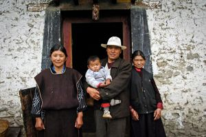 Three generations of a Milin village family, Tibet photographed outside their home. © Forest McMullin