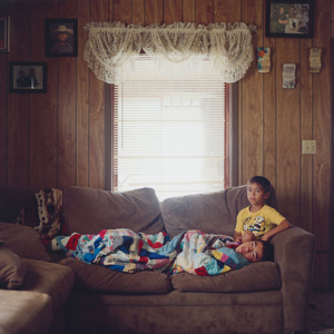 Hudson, 13, and his younger brother Alex, 8, watch TV on a Sunday morning while their mother makes traditional fried bread from scratch in the kitchen.