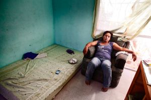Reyna Patricia without anything to do in his house next the bed where he brings his clients. © Meeri Koutaniemi