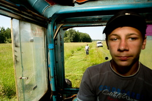 Vova in the tractor cabin and his foster father in the background near the village of Molot.
