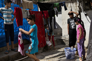 Displaced children from Falluja hang their washing on ropes outside the basement  where they have been living for the past year and a half. 11 families live in the building, each of them using a 3 by 4 meters' room for which they pay 300.000 IQD (250 USD). 29/08/15. Shaqlawa, Iraq.