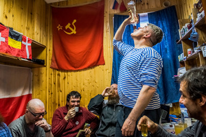 The winter expedition crew of Russian research team and a Chilean scientist drink Samagon, a homemade vodka, in a bedroom of the Bellingshausen Antarctica base; Fildes Bay, Antartica, 28 November 2015.