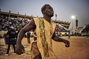 A wrestler trains for a final fight in the Iba Mar Diop stadium, a part of the Medina district of Dakar. This is endowed with 7000 CFA (approx. 1200 US dollar). For the preparation he dances himself to ear-deafening hypnotic drums and repetitive songs in a state similar to trance.