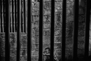Abdoulaye, 15, is a talibe imprisoned in a room with security bars to keep him from running away. Thies, Senegal, 18 May 2015.
