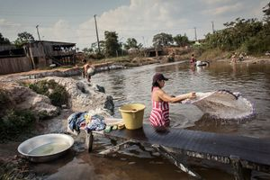 A woman is wahing the clothes in the Igarapé Ambé not far away from the favela of Invasão dos Padres, which will be flooded by the waters of the Xingu as soon as the dam will be built.   © Dario Bosio/Parallelozero