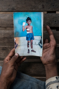 Te Denar (10) at home holds a photograph of himself.
