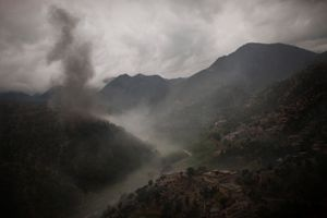 Smoke rises from a U.S. bomb dropped on a suspected insurgent position as a patrol of troops from the 1st Infantry Division comes under attack in the Korengal Valley, Afghanistan, on April 15, 2009. A U.S. soldier was killed by an IED before the patrol came under insurgent fire. © Adam Ferguson