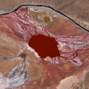 Laguna Roja, Chile. It looks as if a giant had emptied a bucket of red paint on this plateau in the unpopulated mountains of the Parinacota volcano region in northern Chile.The blood-red water that collects in the Laguna Roja has a temperature of 40–500 C (104–1220 F). The vivid colour is due to thermophilic red algae that thrive at these high temperatures.