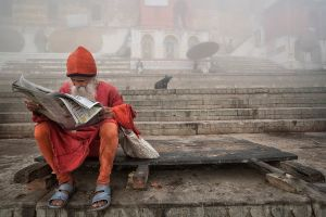 Varanasi, India: A Sadhu is reading daily news on the banks of holy river Ganges. © Matjaz Krivic