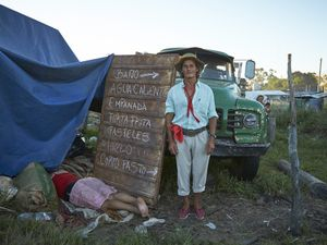 Gauchito Gil devotee posing for the portrait while his partner is asleep after the long day of celebrations  of January 8, date of the murder of the popular saint