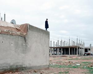 SYRIA. Ayn Al Arab. (Kurdish: Kobani / Kobane). December 2014. A civilian watching an airstrike.