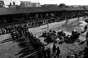 General view on the makeshift shelter where around 1,000 refugee living.Men queue for lunch provided by volunteers at the barracks in Belgrade, Serbia.