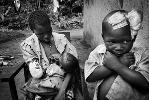 Maria, a mother of three, lost her arm defending her children in Nizi, northeastern Congo. She recounts the story of soldiers eating her flesh after they had hacked off her arm. 2003.