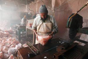 An expert salt cutter inspects a large piece of rock salt so as not to crack it whilst cutting it at factory near Kalabargh.