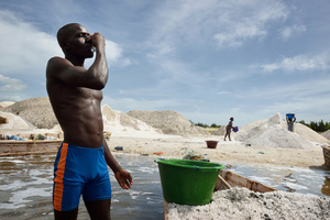 A salt miner drinking from a plastic bag of fresh water. The plastic bags are sold on along the shore of the lake. This hard manual work at a lake with a salt-saturation of about 40% threatens the worker´s health.