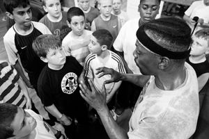 Coach is saying a motivational speech. Boxing for the children is not just sport, it's an adventure, nurturing of manhood, even boast in front of their friends. Right motivation is essential in an upbringing the good boxer from his young days.