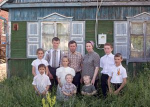 Family of ten in Petrovka in front of their old house which will be ­demolished soon, Petrovka, Omsk Oblast, Russia, 2014