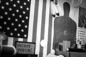 Dallas, Texas, 2010. The walls of a survivalist's garage are plastered in American flags, obliterated target sheets and expired National Rifle Association cards. © Spike Johnson