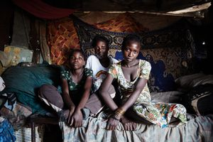 Irene, Cecilia and Maria (from left to right) sit on their bed in their shack in Havana, a quarter of the Katutura township. The three sisters were sold to men by their mother who was an alcoholic. With the help of Father Hermann, Cecilia and Maria brought their mother to jail after their sister Irene died in 2010.