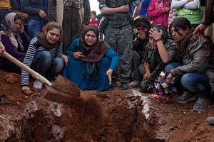 At a cemetery in Kobane, Syria, on 14 April, 2015, families and friends mourn around the grave of Ageri, a Kurdish female fighter who was killed during clashes with the Islamic State in Eastern frontline of Kobane, Syria.