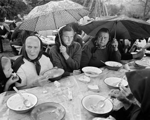 After the Funeral, Valeni, 2000. After the body is buried, mourners return to the deceaseds home for the feast. Because a funeral service typically lasts four hours, appetites have peaked. No manner of bad weather will discourage the crowd. © Kathleen Laraia McLaughlin.