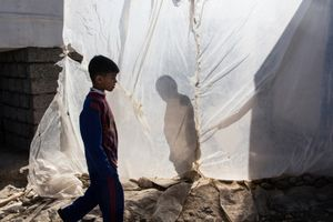 22/01/2015 -- Kirkuk, Iraq -- An Iraqi boy with the Barcelona football club's t-shirt walks among tents and plastic sheets in the Laylan IDP cam in south of Kirkuk.