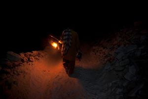 A salt miner leaves the Kalabagh salt mine using only the light from his oil lantern.
