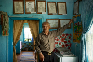 Alexey in his house in Bergul village, showcasing a gallery of portraits created by himself.