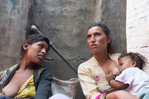 Binata (left) 17, chats with her sister-in-law as she feeds her young baby.