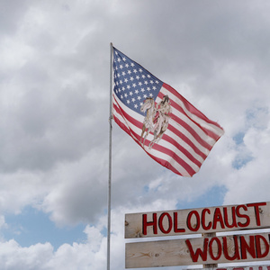 A flag waves outside the Wounded Knee Holocaust Museum on the Pine Ridge Indian Reservation in South Dakota. The Wounded Knee Massacre was one of the biggest tragedies in Native American history which it was triggered by Chief Sitting Bull's death.