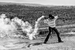 A Palestinian man throws a tear gas grenade back at Israeli forces in the village of Bil'in. Mar. 18, 2011. West Bank, Palestine.