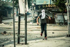 A far left-wing protester of PKK youth organisation YDG-H on the run during clashes with riot police at anti-government demonstration in Istanbul's Gazi neighborhood, Turkey.