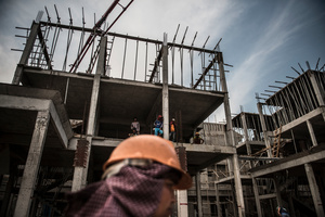 Oung Vanak 45 from Srey Rieng Province walks past a house under construction whilst male workers look down from the building.