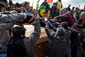 At a cemetery in Kobane, Syria, on 2 April, 2015, Kurdish men take out a corpse of a fighter from a coffin before lowering it into the ground, as people attend the funeral of a Kurdish People's Protection Unit (YPG) who was killed during clashes with the Islamic State in one of the frontlines of Kobane, Syria.