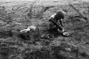 A girl playing on the road. Millions of years ago, there was a sea at current location  of Vasyugan swamp, that's why the soil here is sandy and children can find a natural sand yard to play at any place along the village road. Noviy Vasyugan. Tomsk region. Russia. 2009.