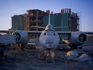 A dumping ground for an abandoned Russian-era bomber that has now been incorporated into the car park of Shamshad TV, a new media company supported heavily by American money. © Simon Norfolk.