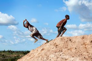 Two boys are playing on a pile of ore dust which contains gold and other metals such as lead. © Alex Masi