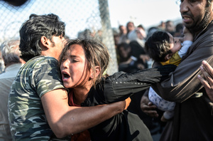 A refugee man holds a crying girl as others rush through broken down border fences to enter Turkish territory; Sanliurfa, Turkey, 14 June 2015.